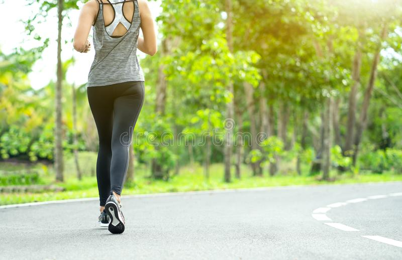 Young fitness sport woman running on the road in the morning, Young fitness sportswoman runner running on tropical park trail. Peo royalty free stock photos