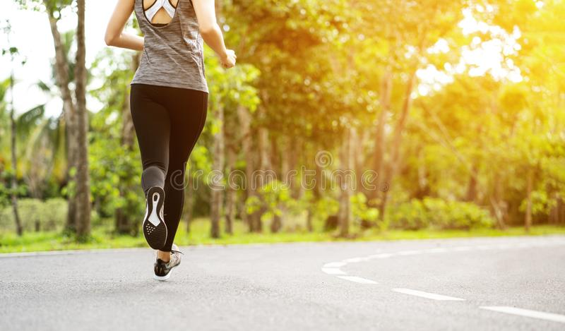 Young fitness sport woman running on the road in the morning, Young fitness sportswoman runner running on tropical park trail. Peo stock photos