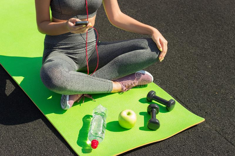 Young fitness sportswoman sitting and using smartphone in gym. Girl on yoga mat with botte of water, dumbbell and ealthy apple royalty free stock images
