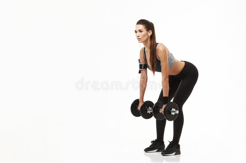 Young fitness sporty girl in headphones training holding dumbbells over white background. Copy space stock images