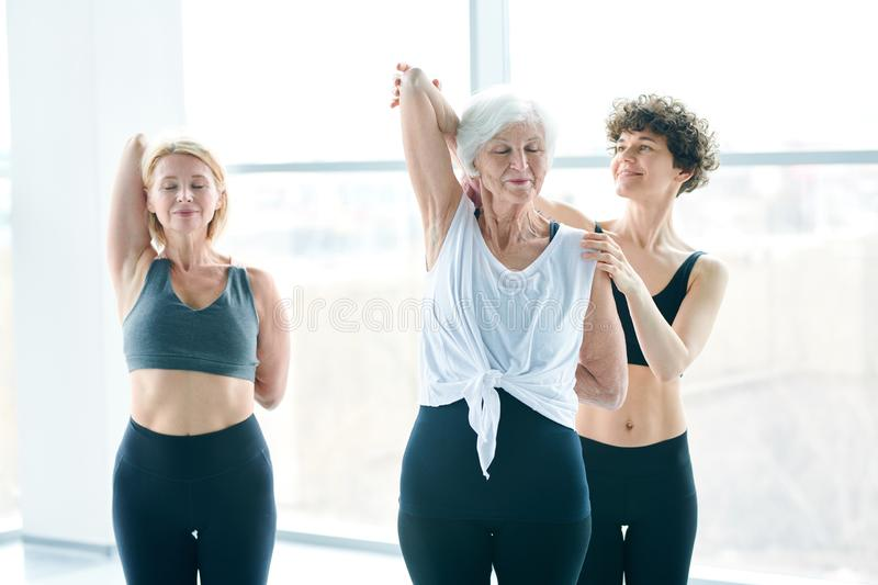 Exercise for back. Young fitness trainer helping senior white-haired women to put her hands behind back during exercise for stretching stock photography