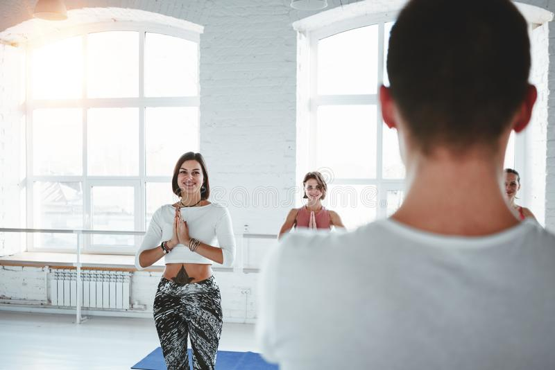 Young fitness trainer teaches a group of women to do yoga stock photo
