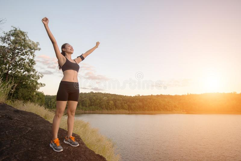 Young fitness woman achieve hiking on peak with lake view sunset stock photos