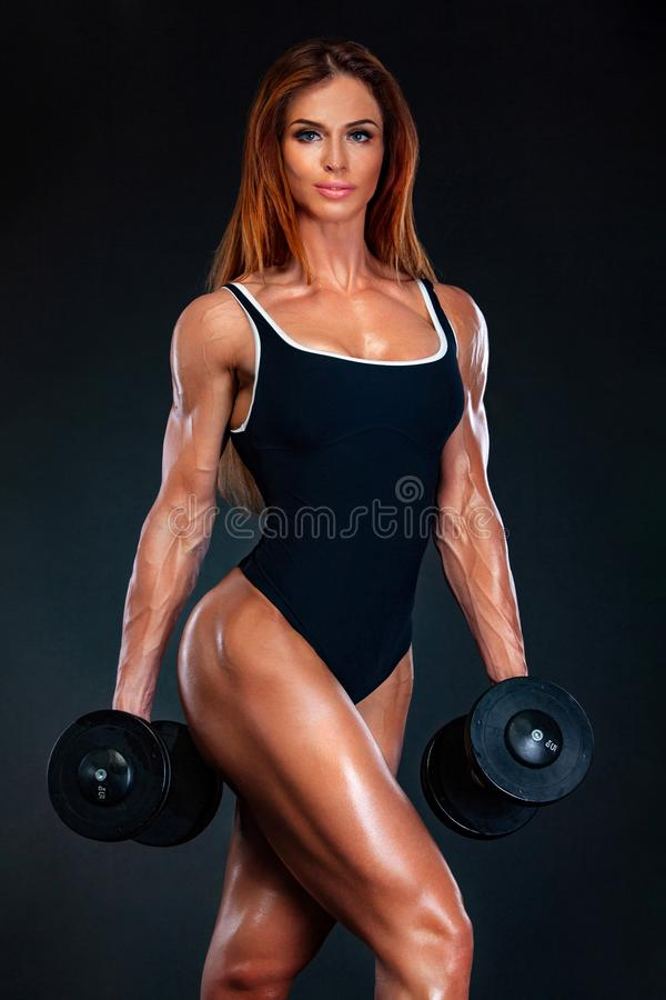 Young fitness woman athlete and bodybuilder with dumbell. Individual sports. Sports recreation. Attractive young fitness woman holding dumbell. Studio shot royalty free stock images
