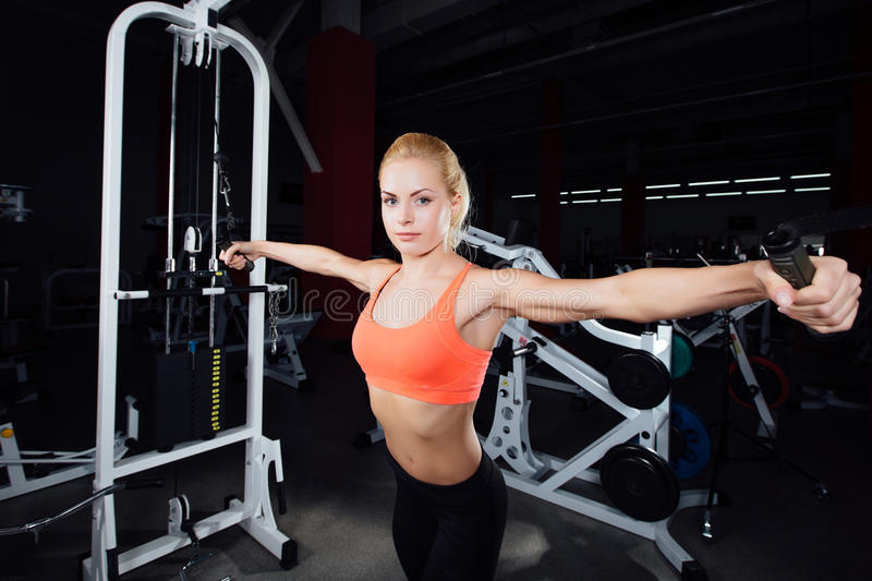 Young fitness woman demonstrate crossover exercises. The pectoral muscles, hard training with exercise-machine Cable. Crossover in gym royalty free stock images