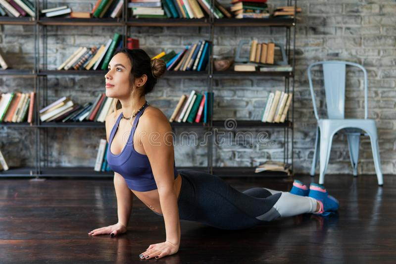 Fitness woman doing cobra pose during yoga workout on floor at home. Young fitness woman doing cobra pose during yoga workout on floor at home stock photos