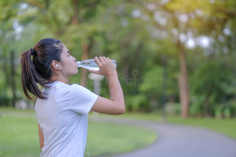 Young fitness woman drinking energy water during walking in the park outdoor stock photography