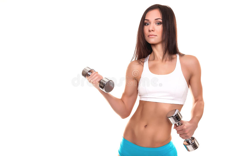 Young Fitness Woman with Dumbbells on White Background. Young Fitness Woman with Dumbbells, wearing gym clothes blue and white and looking at camera at studio on royalty free stock image