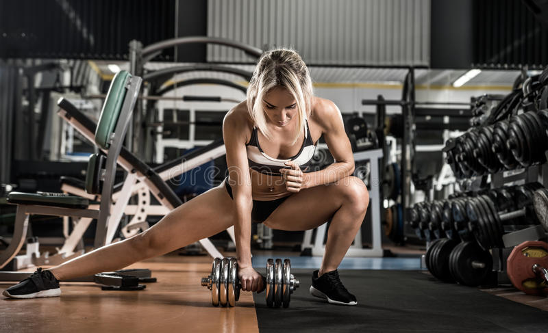 Young fitness woman. Execute exercise with dumbbells in gym, vertical photo stock images