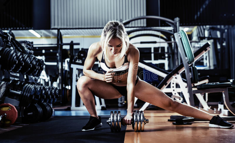 Young fitness woman. Execute exercise with dumbbells in gym, vertical photo stock photography