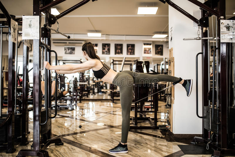 Young fitness woman execute exercise with exercise-machine Cable Crossover in gym royalty free stock photos