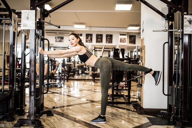 Young fitness woman execute exercise with exercise-machine Cable Crossover in gym. Horizontal photo stock photography