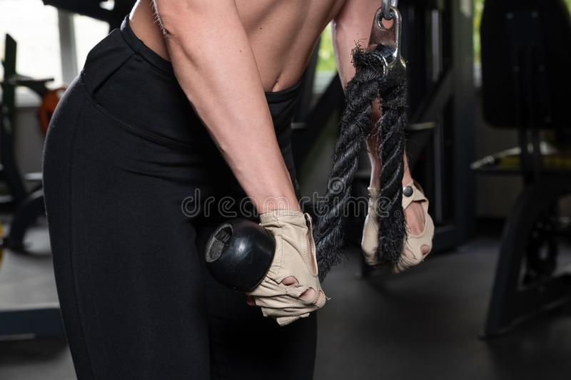 Young fitness woman execute exercise with exercise-machine Cable Crossover in gym, horizontal photo. Girl, female, equipment, body, healthy, lifestyle, weight royalty free stock images