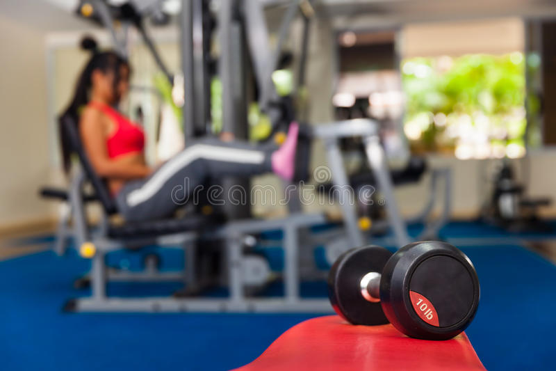 Young Asian girl exercising in the gym to strengthen muscle mass and body slimming royalty free stock image