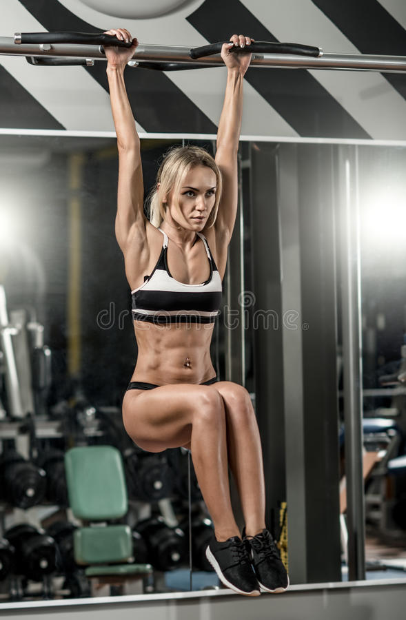Young fitness woman. Execute exercise on horizontal bar in gym, vertical photo royalty free stock image