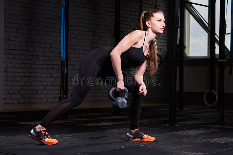 Young fitness woman exercising cross fit with kettlebell against brick wall in the gym. stock photos