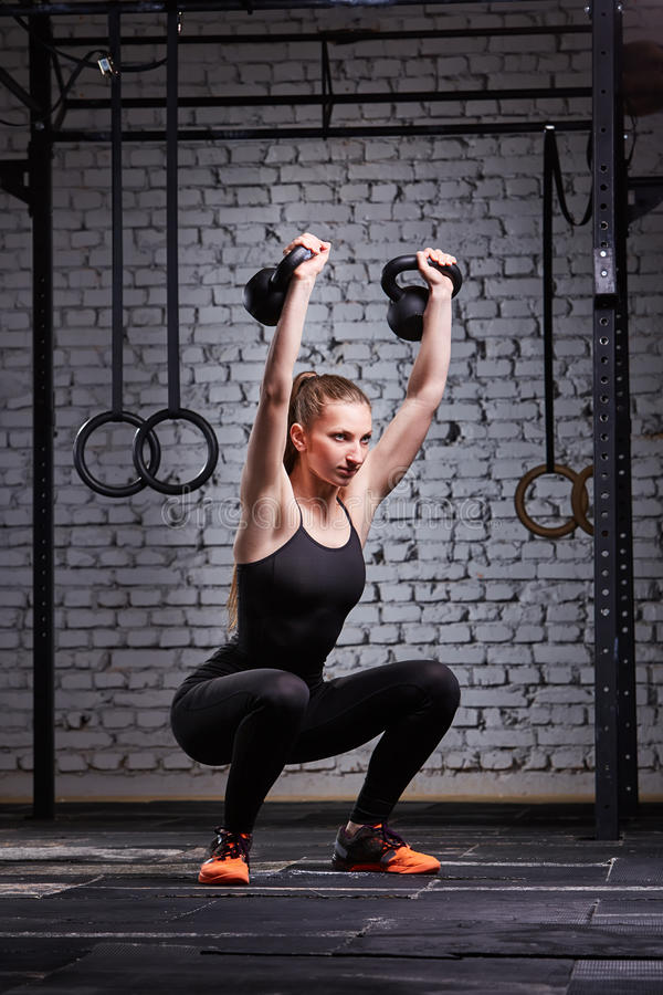 Young fitness woman exercising cross fit with kettlebell against brick wall in the gym. royalty free stock photos