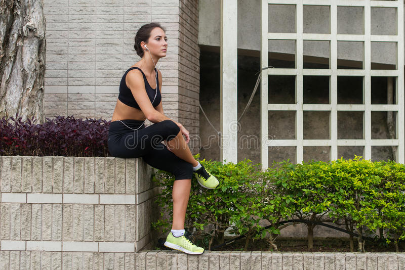 Young fitness woman having rest after running in city. Tired sporty girl sitting and listening to music in headphones stock image