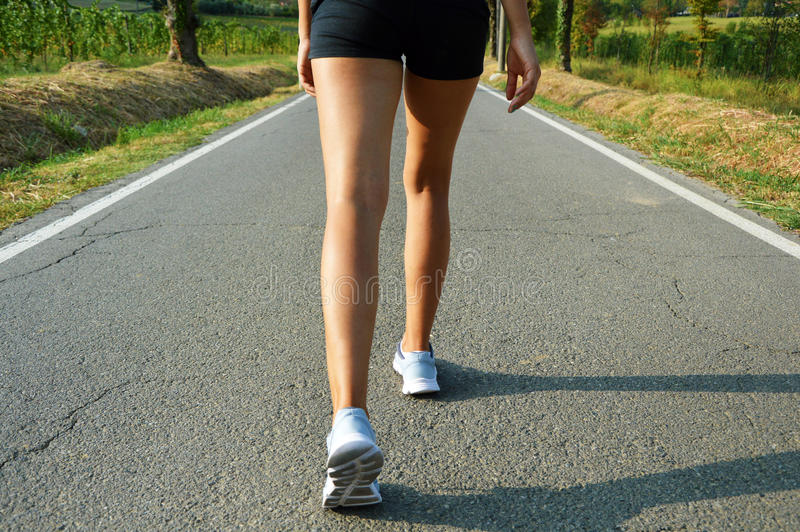 Young fitness woman legs running on asphalt road. stock photography