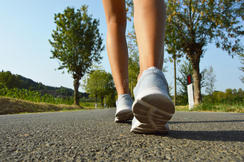 Young fitness woman legs running on asphalt road stock photo
