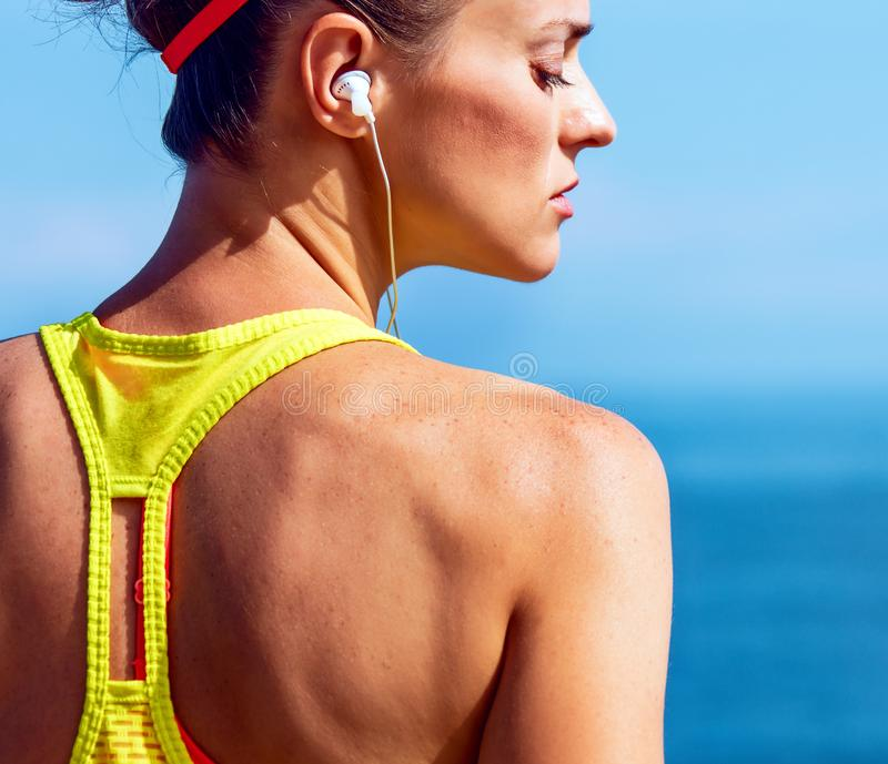 Young fitness woman listening to music at embankment stock photos