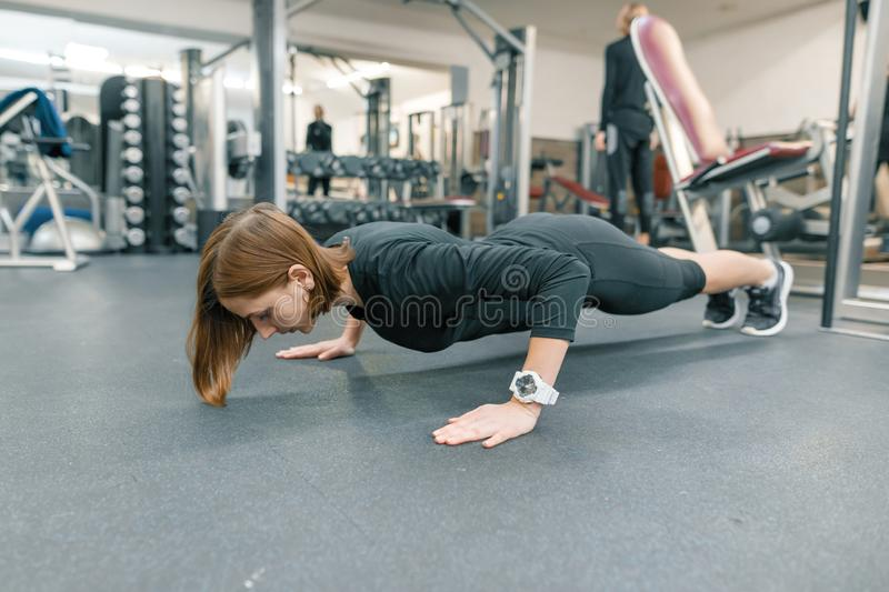 Young fitness woman making push-up exercises in gym. Sport, fitness, training, healthy lifestyle concept.  royalty free stock photography