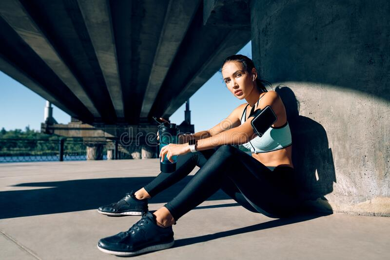 Young fitness woman relax after work out exercising in industrial city background near river stock photo