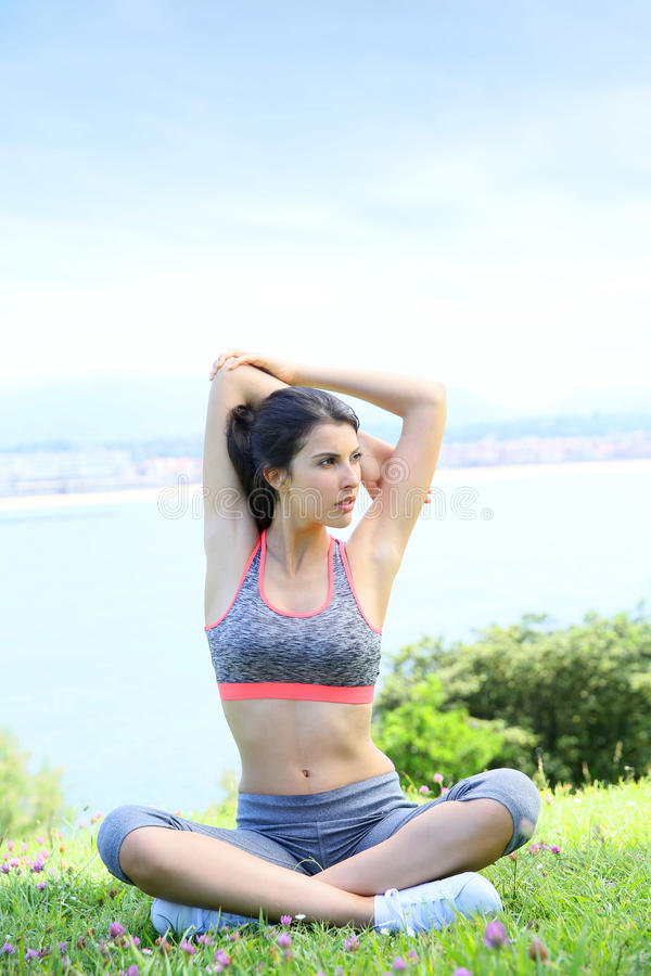Young fitness woman relaxing by the seaside royalty free stock images