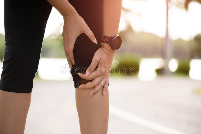 Young fitness woman runner feel pain on her knee in the park. Outdoor exercise activities concept.  stock photos