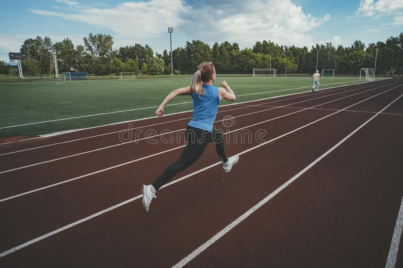 Young fitness woman runner running on stadium track. Athletics at the stadium. royalty free stock images