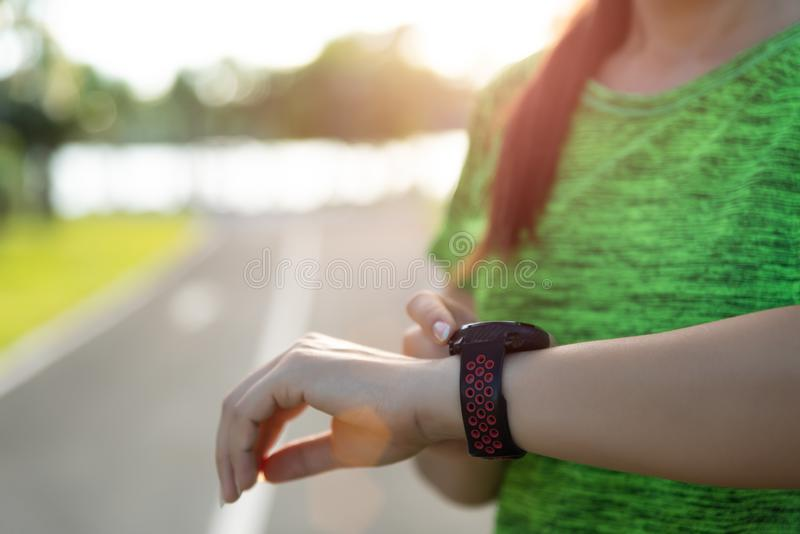 Young fitness woman runner setting up smart watch before running training during sunset. Outdoor exercise activities concept.  stock image