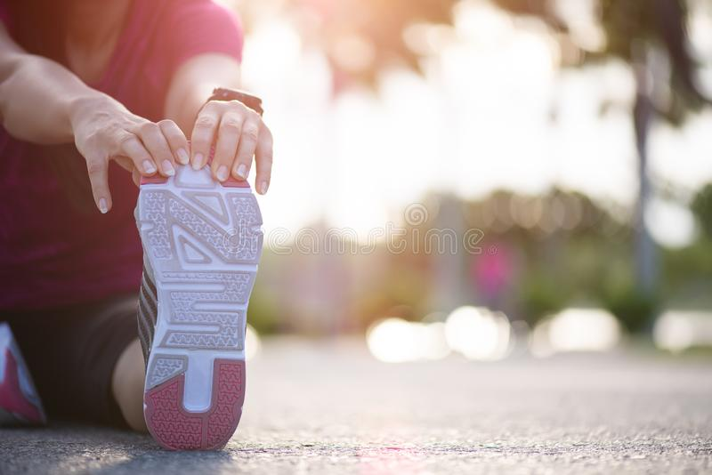 Young fitness woman runner sit on the road stretching legs before run in the park. Outdoor exercise activities concept.  stock photo
