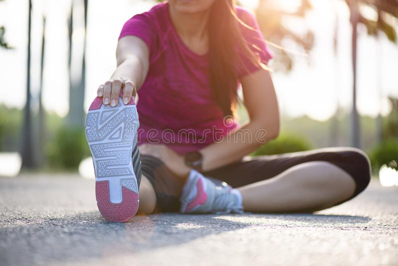 Young fitness woman runner sit on the road stretching legs before run in the park. Outdoor exercise activities concept.  royalty free stock photography