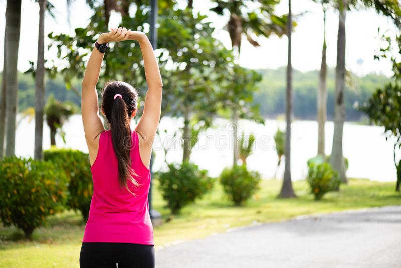 Young fitness woman runner stretching arm before run in the park. Outdoor exercise activities concept.  stock photography