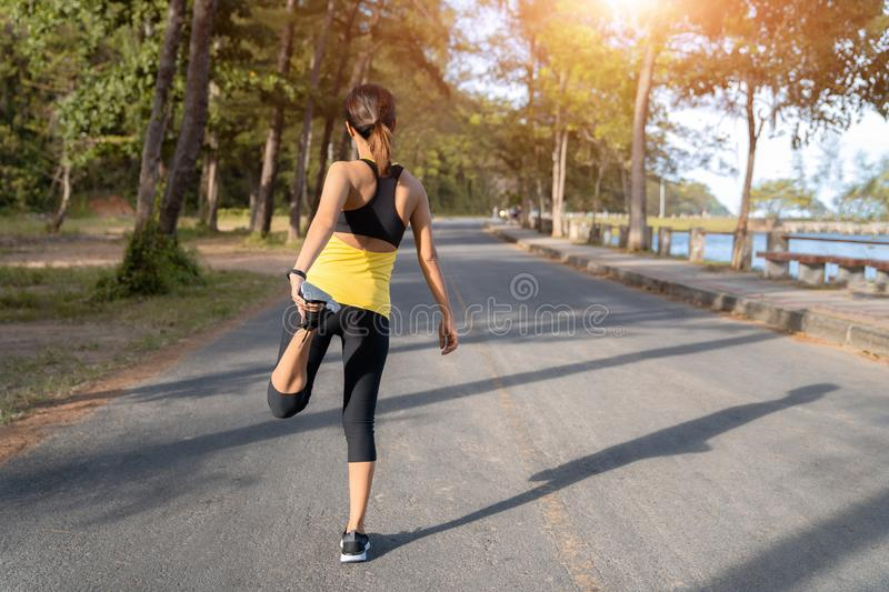 Young fitness woman runner stretching legs before run on city, Young fitness sport woman running on the road in the morning stock images