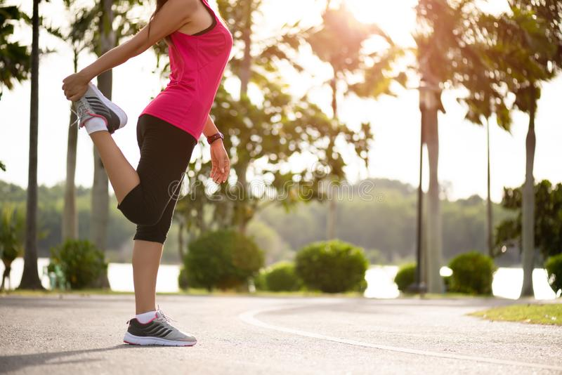 Young fitness woman runner stretching legs before run in the park. Outdoor exercise activities concept.  stock photography