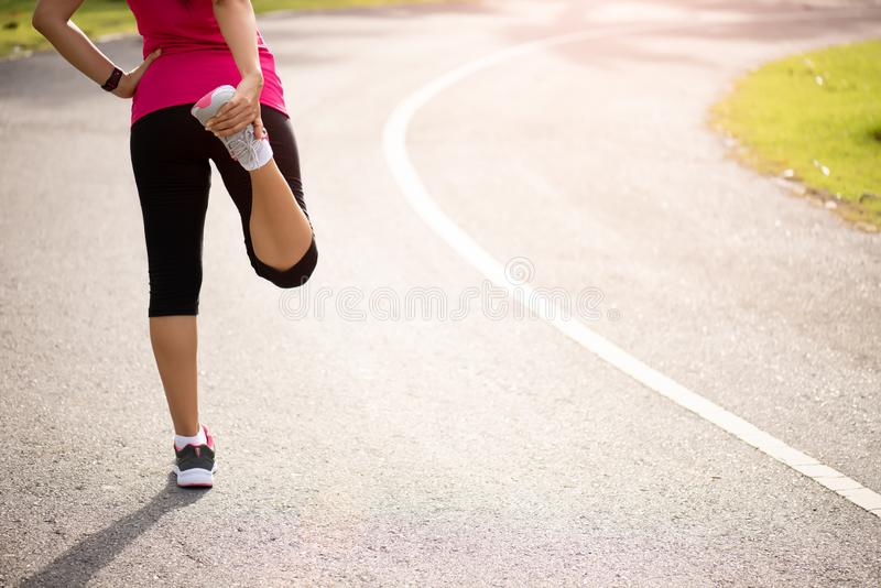 Young fitness woman runner stretching legs before run in the park. Outdoor exercise activities concept.  stock images