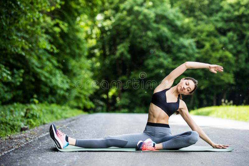 Young fitness woman runner stretching legs before run in the cit stock photo