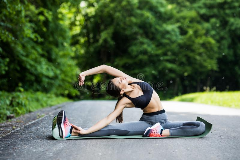 Young fitness woman runner stretching legs before run in the cit stock image