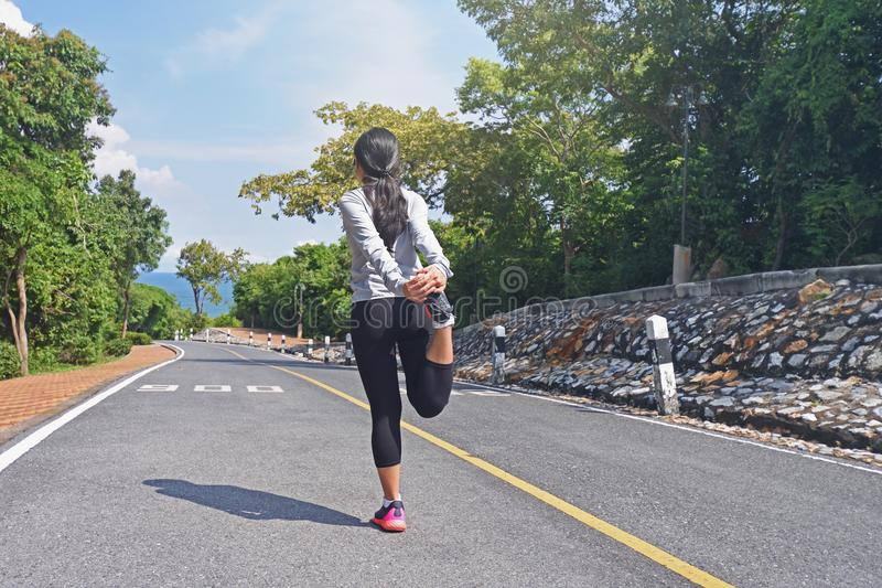 Young fitness woman runner warm up on road before jogging stock photo