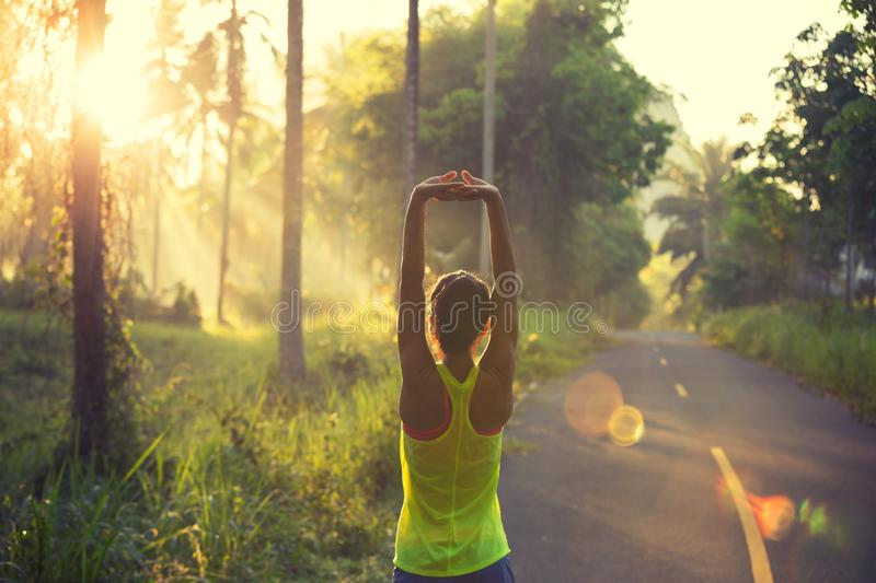 Woman runner warming up on sunrise forest trail stock photography