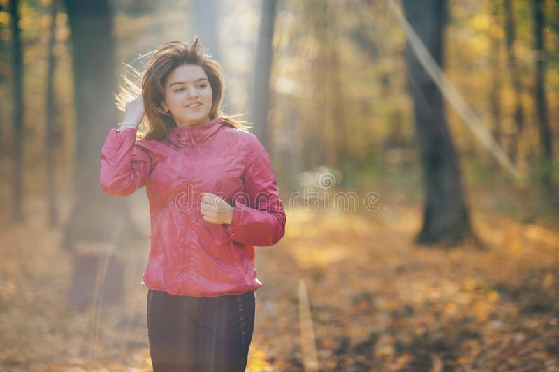 Young woman running on a forest road during sunrise royalty free stock photo