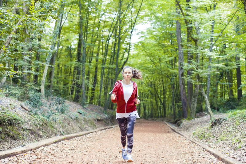 Young fitness woman running at forest trail royalty free stock images
