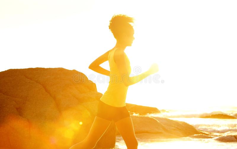 Young fitness woman running by the sea royalty free stock photos