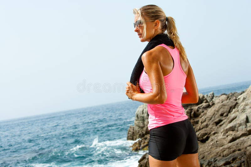 Young fitness woman at seaside with towel. royalty free stock photography