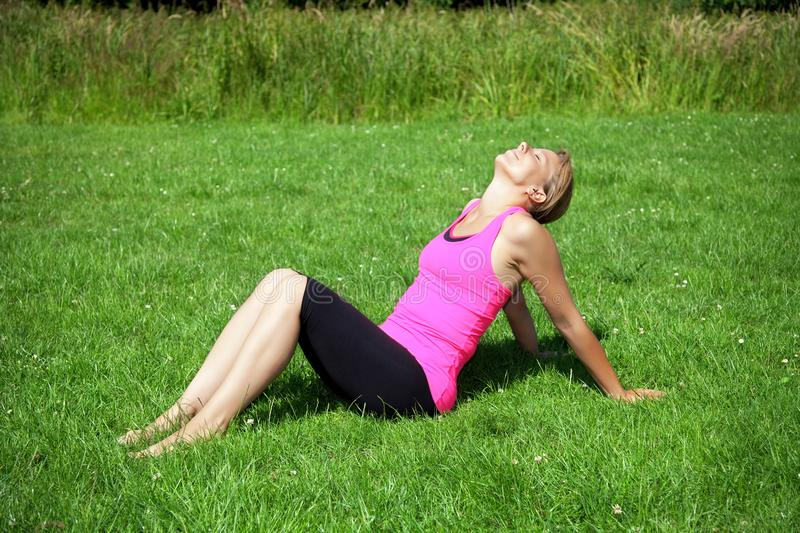 Woman sitting on green grass royalty free stock photo