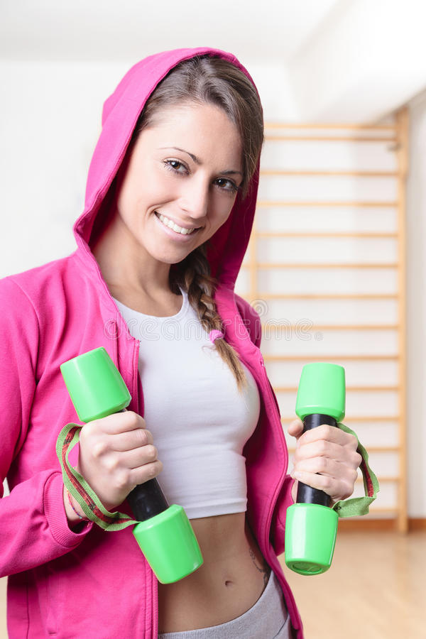 Young Fitness Woman Smiling and Lifting Weights stock photo