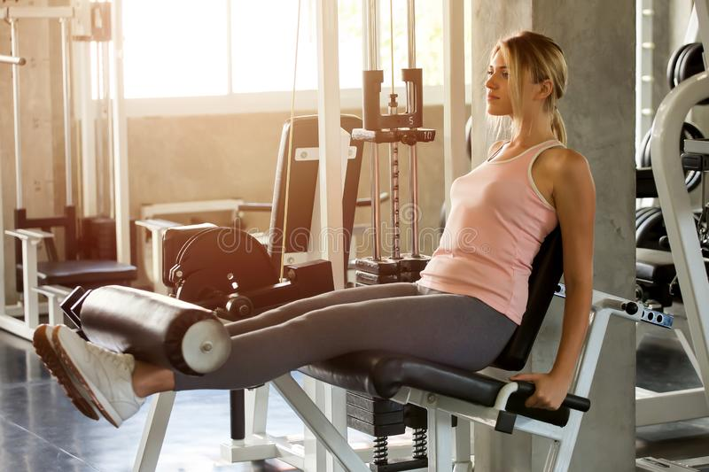 young fitness woman in sportswear exercises open legs muscles with push machine in gym . sport girl workout healthy lifestyle. royalty free stock image