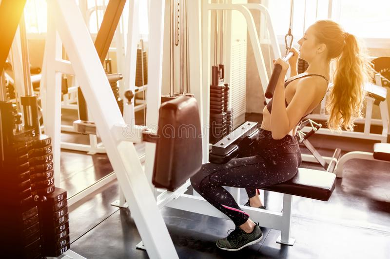 Young fitness woman in sportswear exercising building muscles with machine Cable Crossover in sport gym morning ligth.workout. Exercise, endurance, healthy stock image