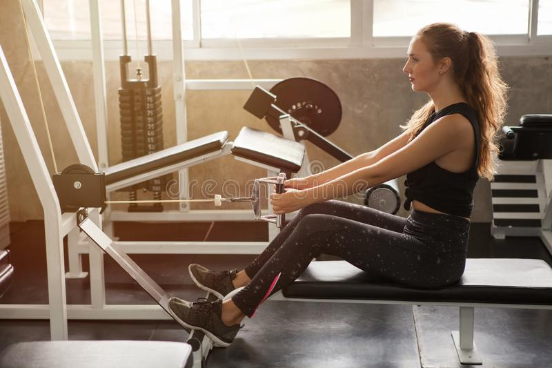 Young fitness woman in sportswear exercising building muscles with machine Cable Crossover in sport gym morning ligth.workout. Exercise, endurance, healthy stock photography
